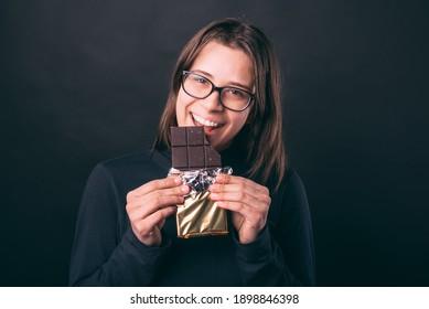 Lächelnde junge Frau, die dunkle Schokolade auf dunklem Hintergrund isst