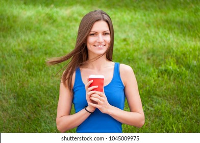 Smiling young woman eating a donut and holding a Cup of coffee outdoors