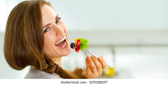 Smiling young woman eating fresh salad in modern kitchen