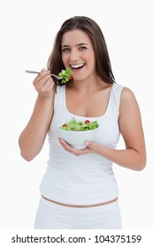 Smiling young woman eating a salad against a white background