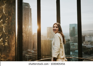 Smiling young woman at elevator window, enjoying the city skyline from the 35 floor, at sunset, with stunning panoramic view of Los Angeles.