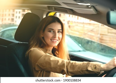 A smiling young woman enjoying driving on a beautiful sunny day