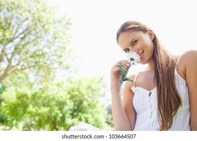 Smiling young woman enjoying the smell of a flower in the park