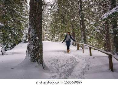 Smiling young woman enjoys winter in beautiful pine forest, walking in fluffy white snow along a hiking trail, scenic nature landscape outdoor travel background, Jasna ski resort, Slovakia (Slovensko)