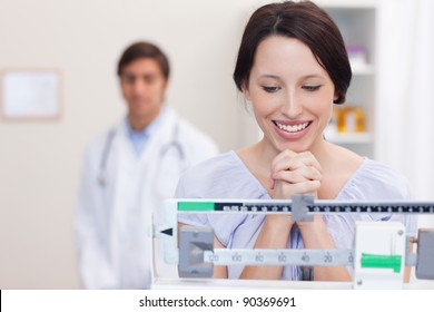Smiling young woman excited about the scale