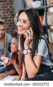 Smiling young woman in eyeglasses talking on smartphone and friends sitting behind