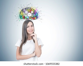 Smiling young woman with fair hair wearing a white T shirt and thinking while looking at the viewer. A gray wall background with a cog brain sketch on it. Mock up