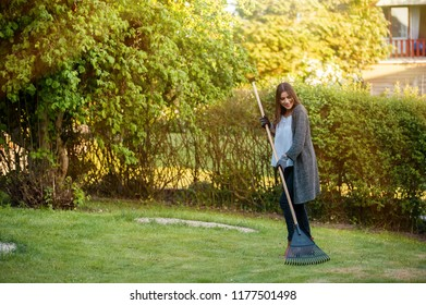 Smiling young woman with garden leaf rake in her home backyard with flowers, plants and vegetation. Gardening as hobby and leisure concept.