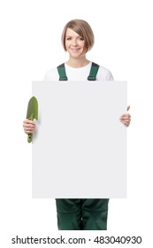 smiling young woman gardener holding banner with empty copy space for your text isolated on white background. advertisement blank board. your text here. gardening service concept