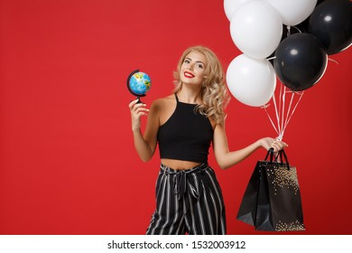 Smiling young woman girl in black clothes posing isolated on red background in studio. Shopping discount sale concept. Mock up copy space. Holding air balloons package bag with purchases world globe