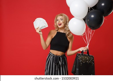 Smiling young woman girl in black clothes posing isolated on red wall background. Shopping discount sale concept. Mock up copy space. Holding air balloons package bag with purchases fan of cash money