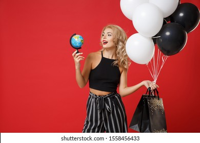 Smiling young woman girl in black clothes posing isolated on red background in studio. Shopping discount sale concept. Mock up copy space. Holding air balloons package bag with purchases, world globe