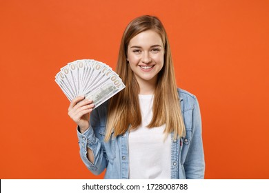 Smiling young woman girl in casual denim clothes posing isolated on orange wall background studio portrait. People lifestyle concept. Mock up copy space. Holding fan of cash money in dollar banknotes