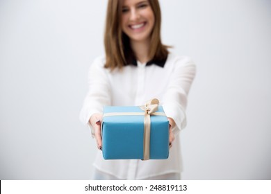 Smiling young woman giving gift. Focus on a gift