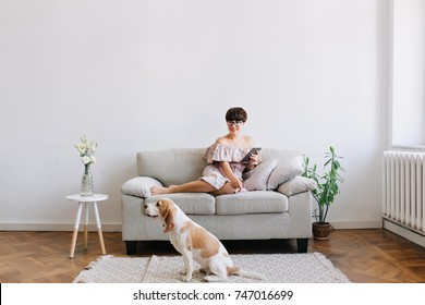 Smiling young woman in glasses looking with smile at beagle dog sitting on carpet beside sofa. Indoor portrait of lovely brunette girl lies on couch with tablet while her puppy resting on the floor.