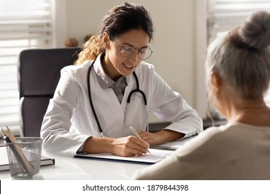 Smiling young woman GP write prescription to mature patient at consultation in hospital. Female doctor consult talk with elderly client in private clinic. Healthcare insurance, geriatrics concept.