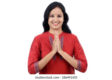 """Smiling young woman greeting """"Namasthe"""" against white background"""