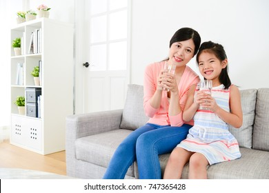 smiling young woman and happy cute little girl sitting on sofa couch and holding glass cup with health drink water looking at camera.