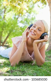 Smiling young woman with headphones enjoying music on the lawn
