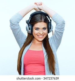 Smiling young woman with headphones listen music. Studio portrait, isolated background.