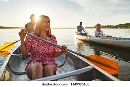 Smiling young woman and her boyfriend canoeing with another couple on a lake on a late summer afternoon