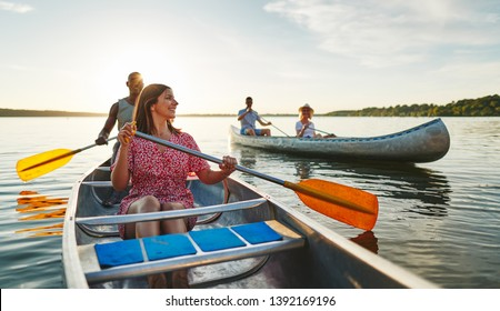 Smiling young woman and her boyfriend canoeing with another couple on a lake on a sunny summer afternoon