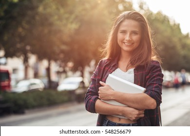 Smiling young woman with her digital tablet in the city