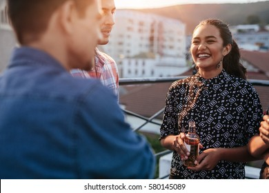 Smiling young woman holding beer standing on rooftop with friends. People having good time at party.