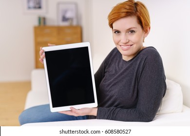 Smiling young woman holding a blank tablet pc with the screen with copy space facing the lens as she relaxes at home on a sofa