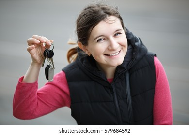 Smiling young woman holding car key on blurred gray asphalt background. Selective focus.