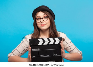 Smiling young woman holding a clapperboard and looking at camera on the blue background.