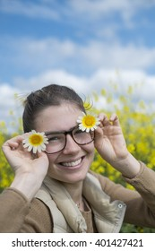 Smiling young woman holding a couple of daisy flowers on both sides of the face under a blue sky with yellow wild flowers in the background