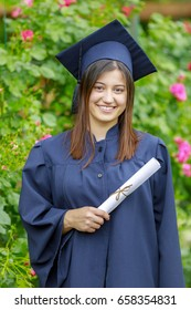 Smiling young woman holding diploma and wearing cap and gown outdoors looking at camera. Graduation concept.