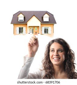 Smiling young woman holding a house on her finger