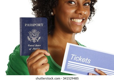 A smiling young woman holding up a passport and generic ticket envelope. The focus is on the passport.