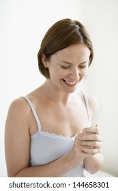 Smiling young woman holding pregnancy test kit