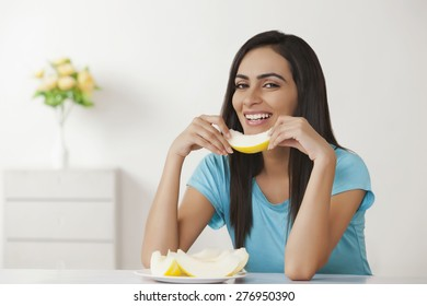Smiling young woman holding slice of melon at home