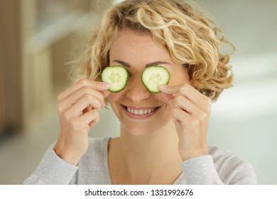 smiling young woman holding slices of cucumber
