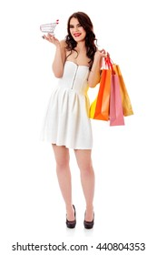 Smiling young woman holding small empty shopping cart and shopping bags