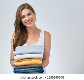 smiling young woman holding stack of foldet clothes. laundry concept.