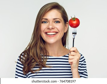 Smiling young woman holding tomato on fork. Isolated portrait with dieting concept.
