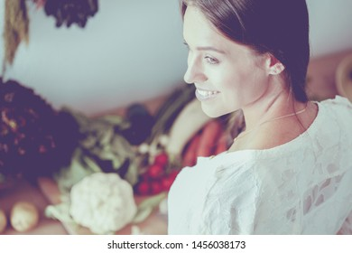 Smiling young woman holding vegetables standing in kitchen. Smiling young woman