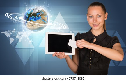 Smiling young woman holging tablet and blank card with glowing 3d Earth model and looking at camera on abstract blue background. Elements of this image furnished by NASA