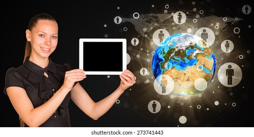 Smiling young woman holging tablet looking at camera. Model of earth on black background. Connection all over the world. Elements of this image furnished by NASA