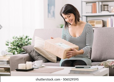 Smiling young woman at home on the couch, she has received a postal parcel, online shopping and delivery concept