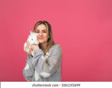 Junge Frau lächeln umarmt weißes Kaninchen. rosafarbener Hintergrund.