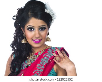 Smiling young woman in Indian traditional clothing looking at camera against white background