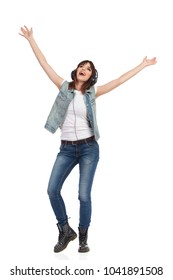 Smiling young woman in jeans and unbuttoned vest is holding arms outstretched, listening music in headphones, singing and looking up. Full length studio shot isolated on white.