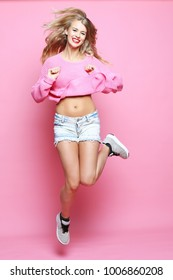 smiling young woman jumping in air over pink background