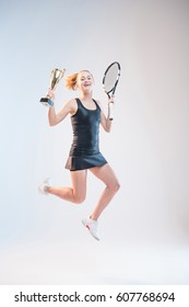 smiling young woman jumping with racket and trophy in hands isolated on white